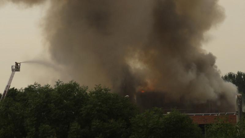 Brand in zuidoost. De brandweer blust brand in de buurt van het Bindelmeercollege. Vanaf hier is onduidelijk te zien welk pand in brand staat.